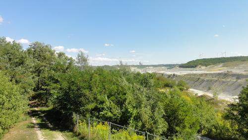 Blick über den Tagebau: Zementfabrik und Windräder
